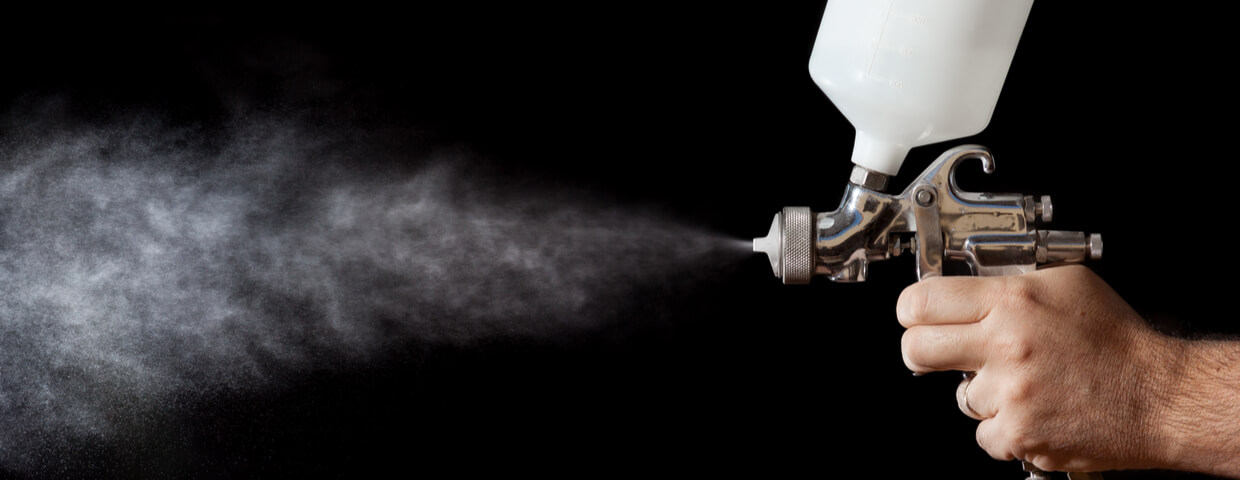 close up of spray gun on black background, spray coating concept